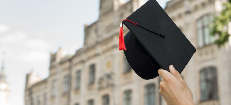 czarna czapka rogatka z czerwonym chwostem na tle budynku