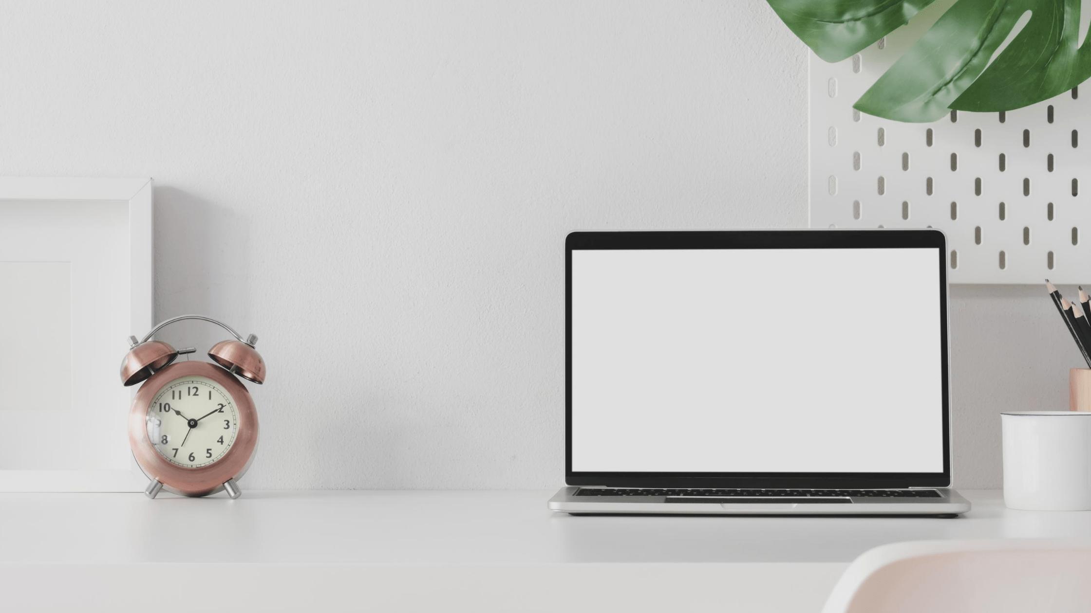 białe biurko na którym stoi złoty zegar stołowy i laptop