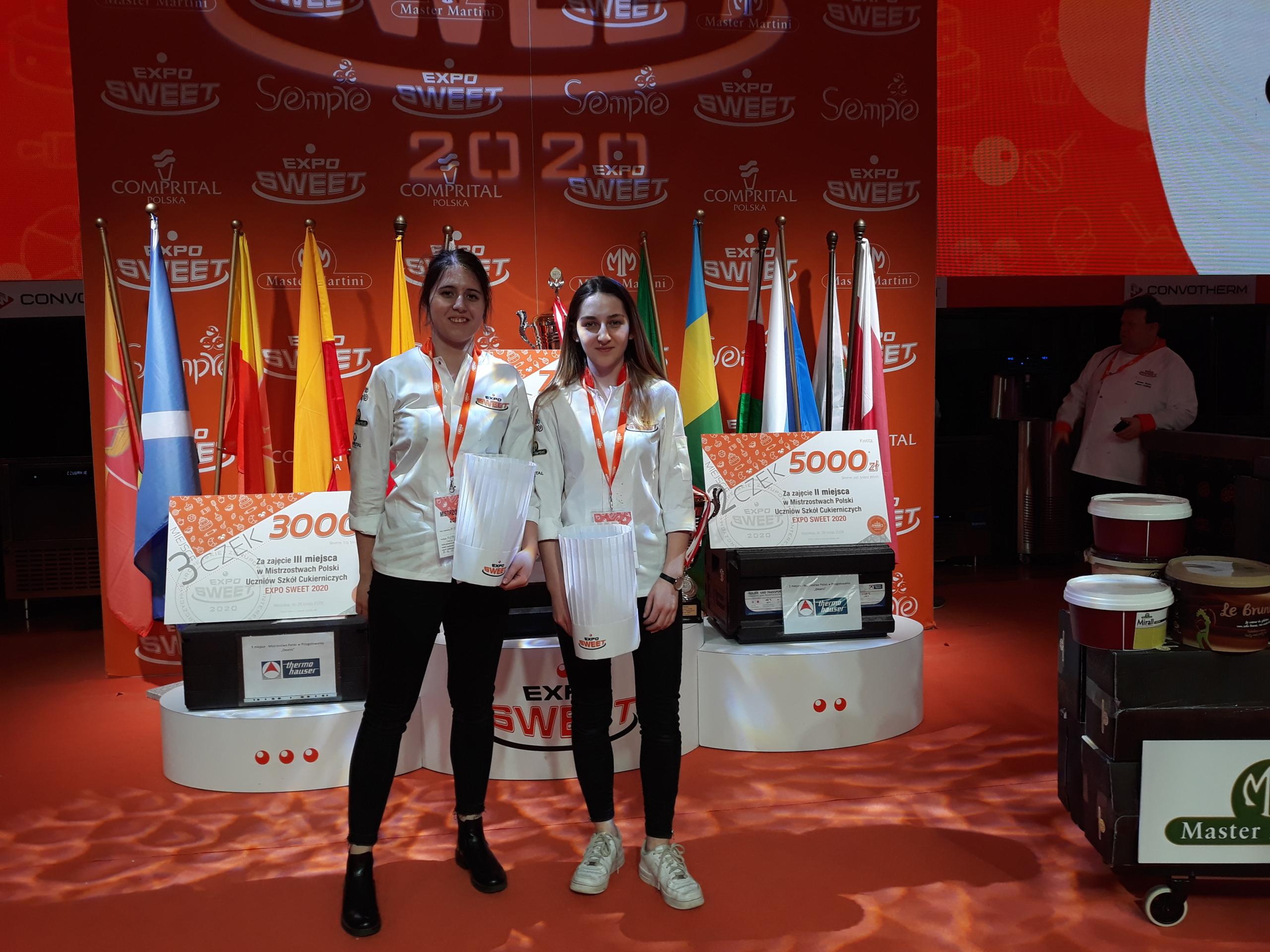 Dwie uczennice na tle ścianki wystawienniczej Expo Sweet 2020