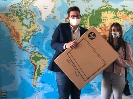 Na tel mapy świata, dwoje uczniów w maseczkach trzyma pudełko z nowym kompterem