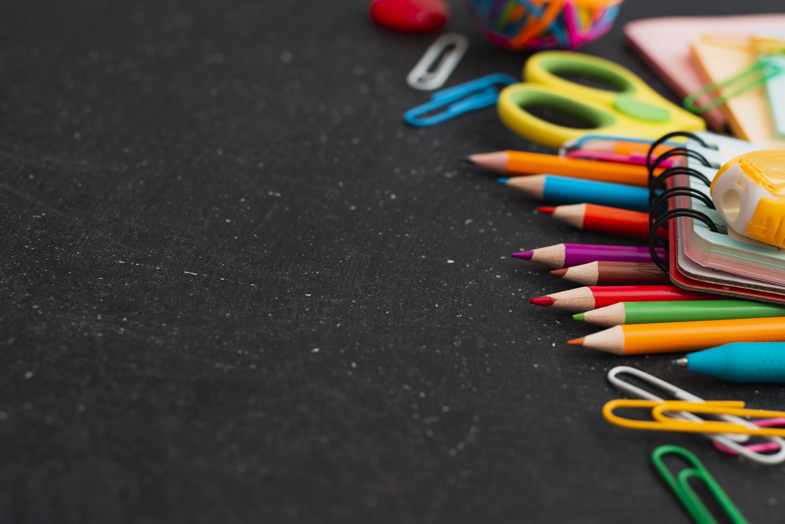 kolorowe kredki i długopisy na czarnym tle