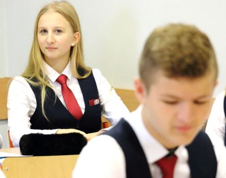 uczniowie w mundurkach szkolnych w sali lekcyjnej