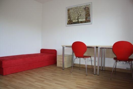 pokój w internacie z łóżkiem i biurkiem