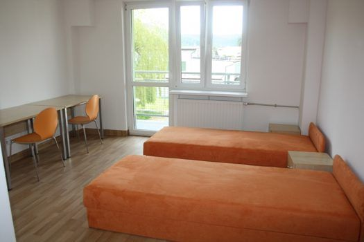 pokój w internacie z dwoma łóżkami i biurkami