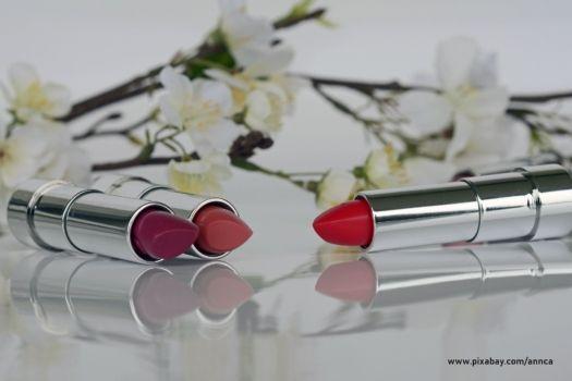 Trzy czerwone szminki na białym tle z kwiatami