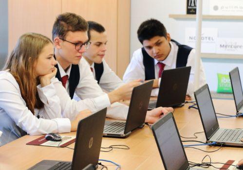uczniowie w strojach szkolnych w sali komputerowej