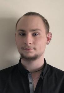 Absolwent Roku 2020, LO. Mężczyzna w czarnej koszuli, z krótką brodą i kilkoma kolczykami w lewym uchu.