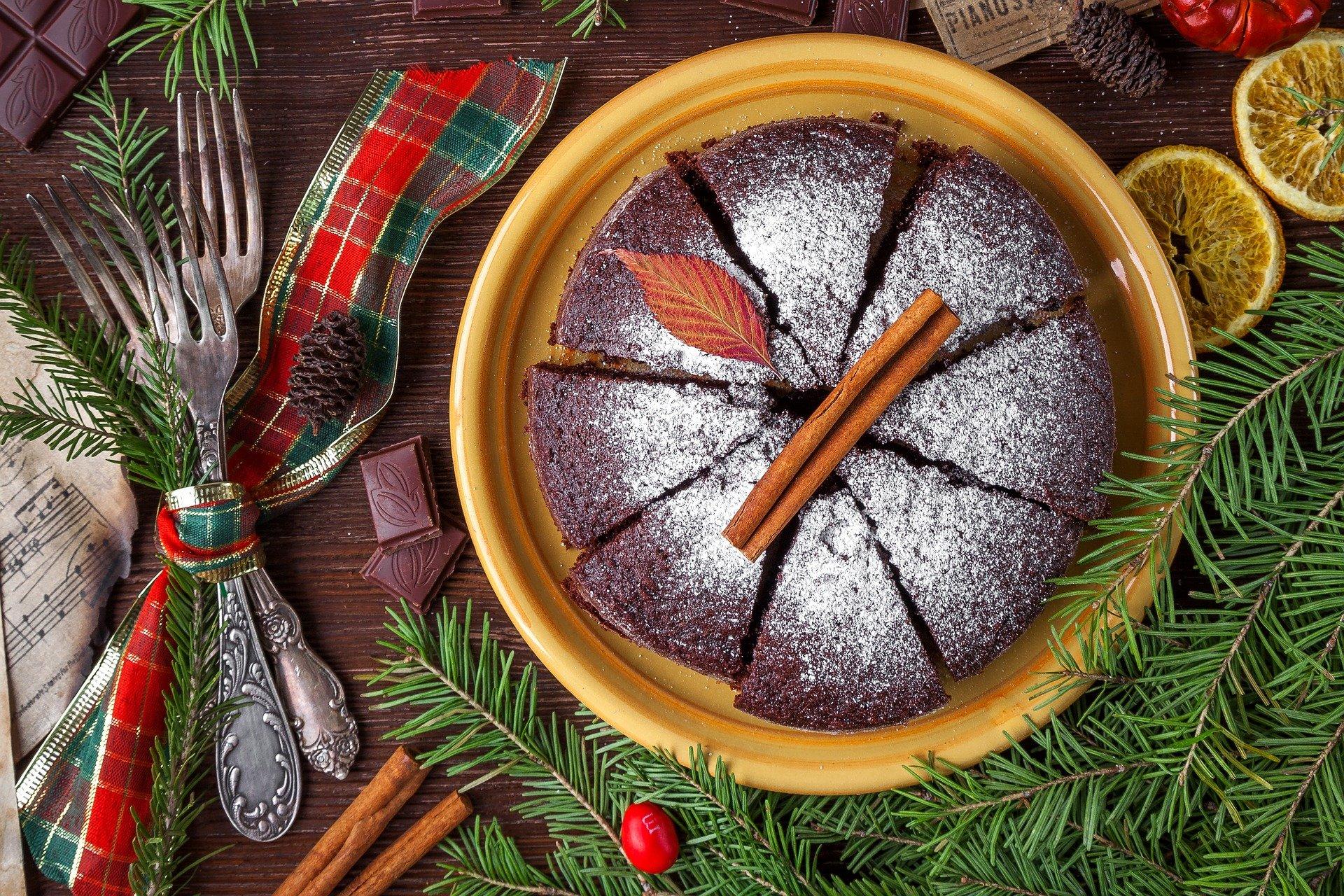 Ciasto świąteczne na żółtym talerzu, obok dekoracja świąteczna z gałązek choinki, cynamonu i suszonych pomarańczy