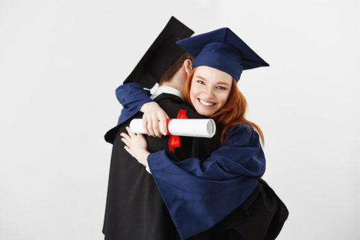 Dwóch absolwentów obejmujących się na białym tle. Dziewczyna trzyma dyplom, uśmiechając się, patrząc w aparat.