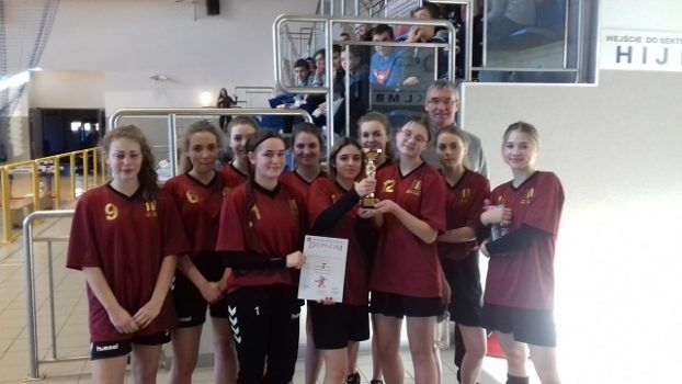 Żeńska drużyna piłki ręcznej pozuje do zdjęcia z pucharem i dyplomem