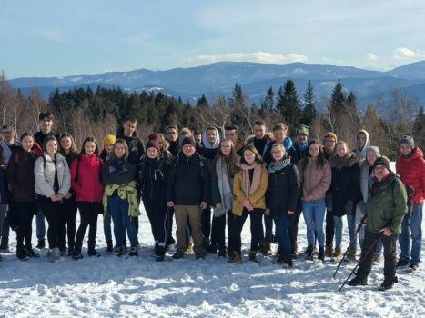 Grupa młodzieży z opiekunami na zimowej wycieczce. Zdjęcie na śniegu, w tle góry i las