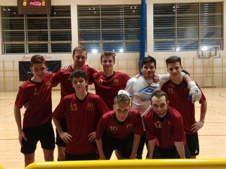Grupa 8 młodych piłkarzy w bordowych koszulkach na sali gimnastycznej
