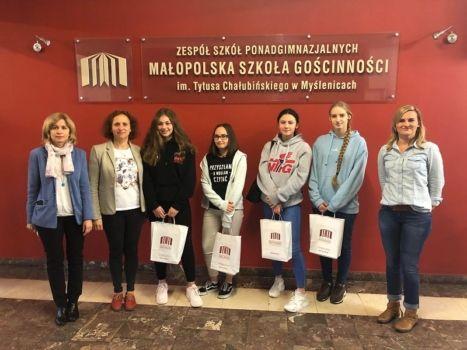4 uczniów w towarzystwie nauczycieli pozują do zdjęcia z nagrodami w konkursie na tle logotypu szkoły
