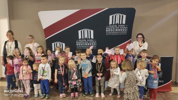grupa przedszkolaków z opiekunami na korytarzu szkolnym