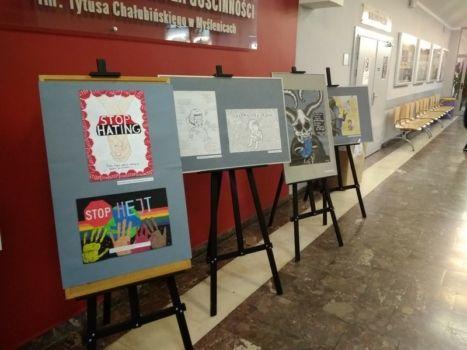wystawa prac uczniów na sztalugach na korytarzu szkolnym
