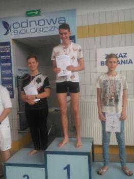 trzech chłopców na podium zawodów pływackich