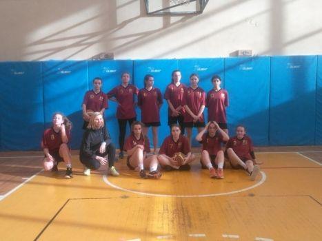 Dziewczęca drużyna koszykówki w bordowych koszulkach na sali gimnastycznej