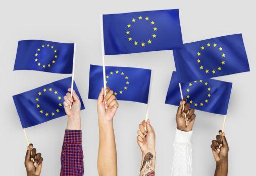 ręce machające flagami Unii Europejskiej