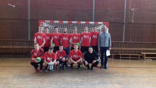 młodzieżowa drużyna piłki ręcznej w czerwonych koszulkach na tle bramki