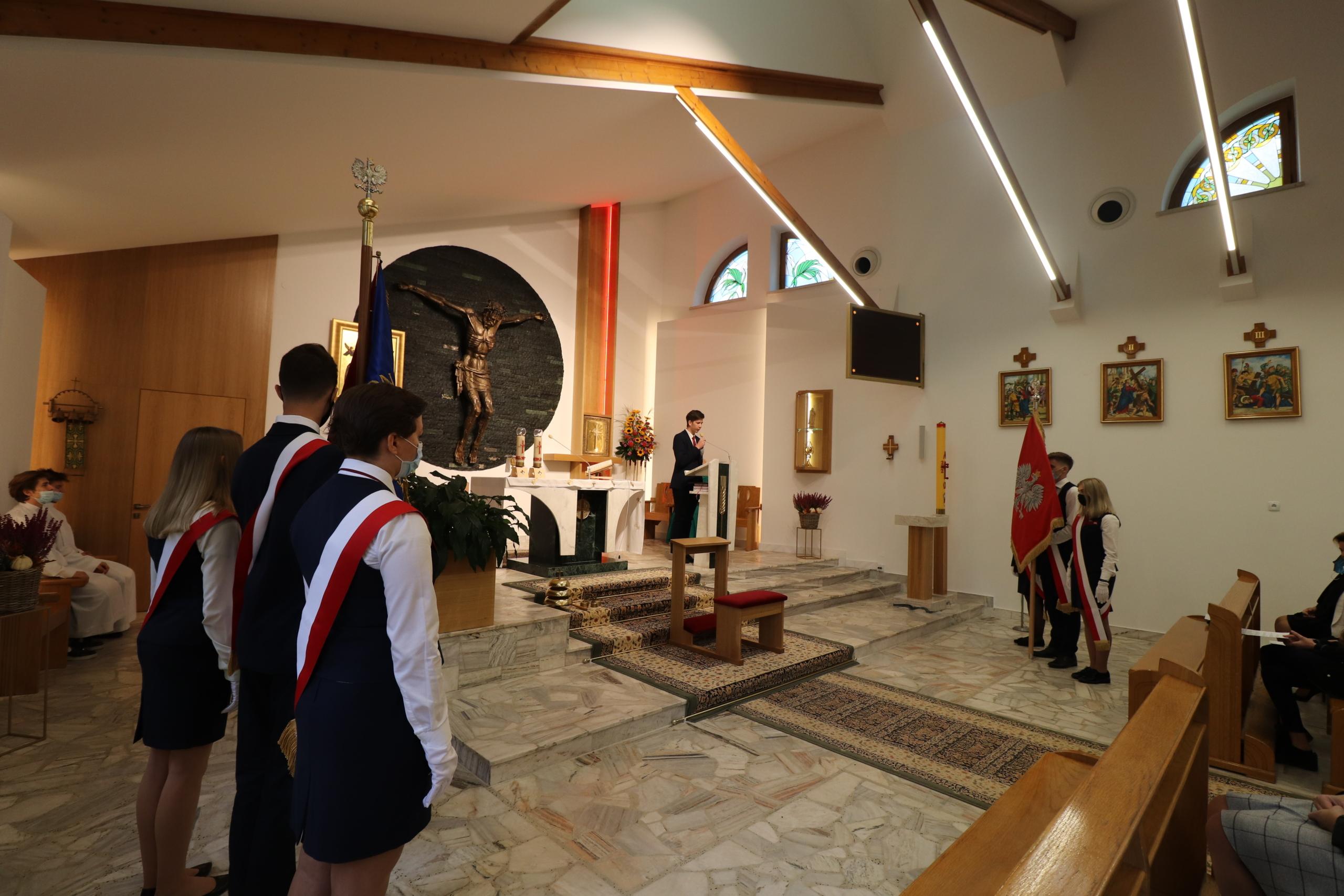 widok na kaplicę kościelną i młodzież ze sztandarem