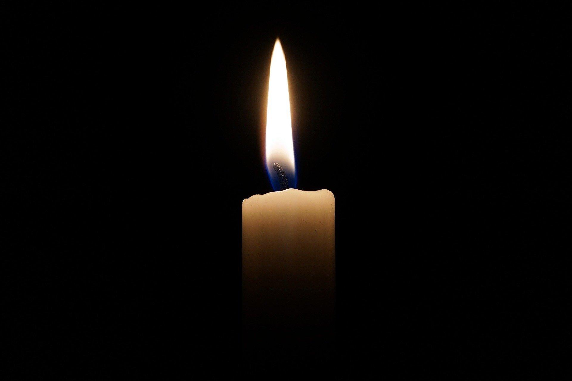 płonąca świeczka na czarnym tle
