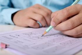 Widok na dłoń z ołówkiem zakreślającą odpowiedzi testu