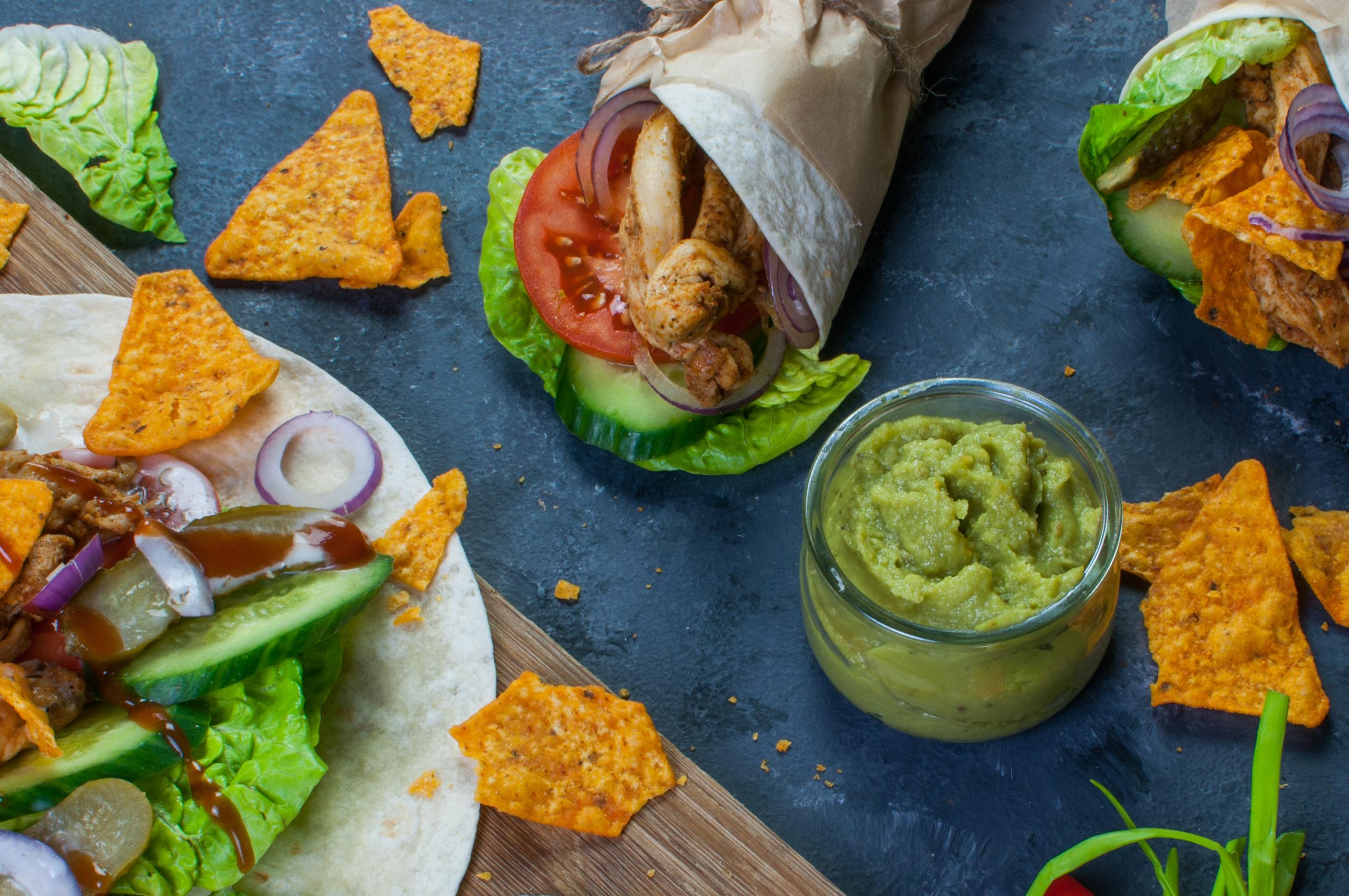 widok na tortille z kurczakiem oraz guacamole i warzywami oraz nachosami