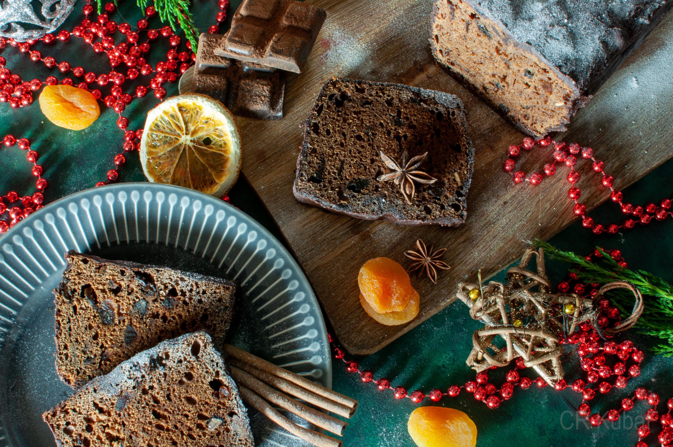 Widok na stół przystrojony bożonarodzeniowo prezentujący pokrojony piernik na niebieskim talerzu.