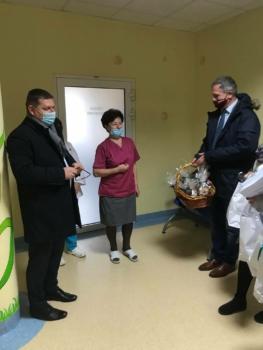 Grupa osób na szpitalnym korytarzu przekazuje podarunki