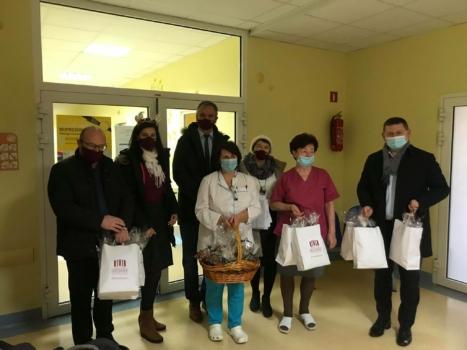 Grupa ludzi w szpitalnym korytarzu trzymająca białe pakunki z piernikami