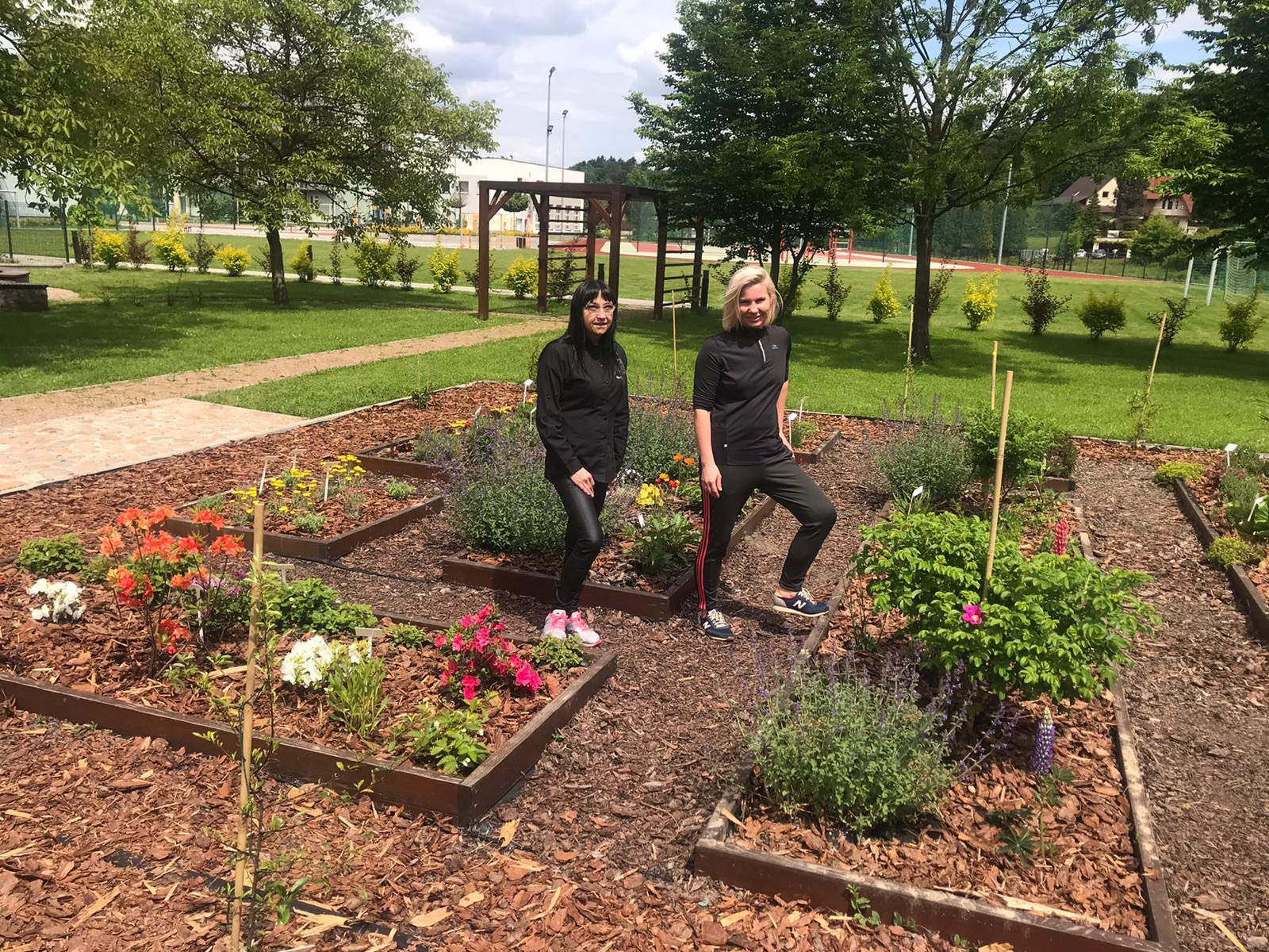 dwie kobiety ubrane na czarno w ogrodzie z kwiatami i ziołami