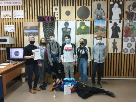 zawody strzeleckie, grupa uczniów z opiekunem na tle ściany z tarczami strzeleckimi