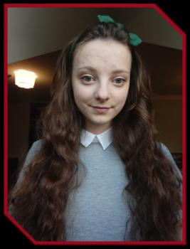 nominowana w konkursie Absolwent roku. Brunetka z długimi kręconymi włosami.