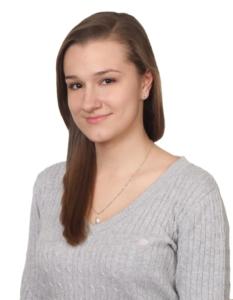 Absolwentka roku 2016, technikum. Brunetka z długimi włosami w szarym sweterku.