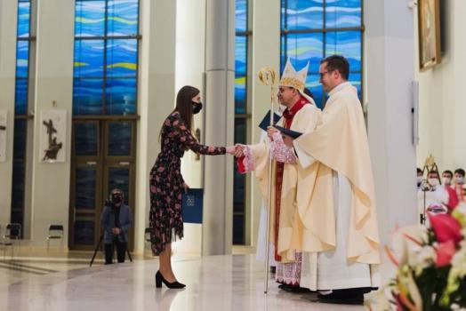 dziewczyna na ołtarzu przyjmuje wyróżniene od biskupa