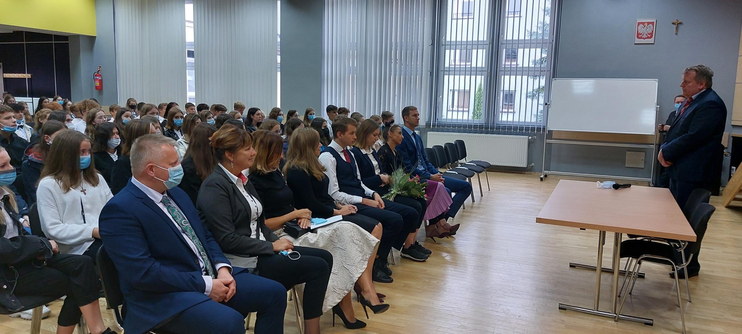 Uczniowie i nauczyciele w auli szkolnej podczas uroczystości rozpoczęcia roku szkolnego
