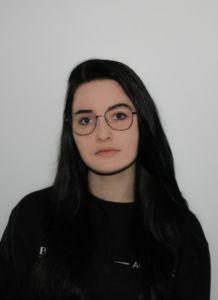 Absolwentka roku 2021 Technikum. Kobieta w okularach z długimi czarnymi włosami, ubrana w czarną bluzę.
