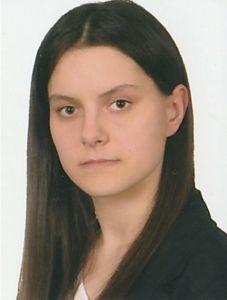 Absolwentka roku 2015, technikum. Brunetka z długimi włosami.
