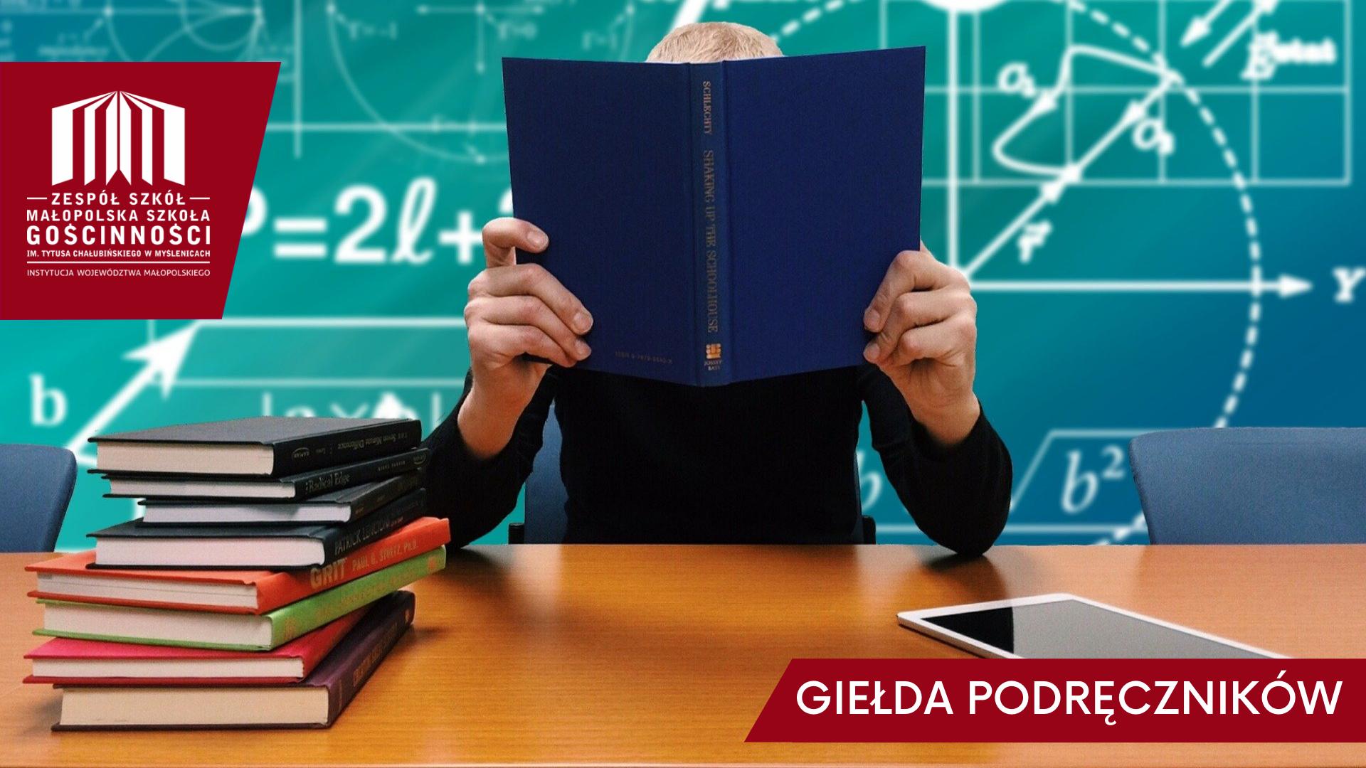 Widok na tablicę kredową i biurko przy którym siedzi uczeń schowany za książkami