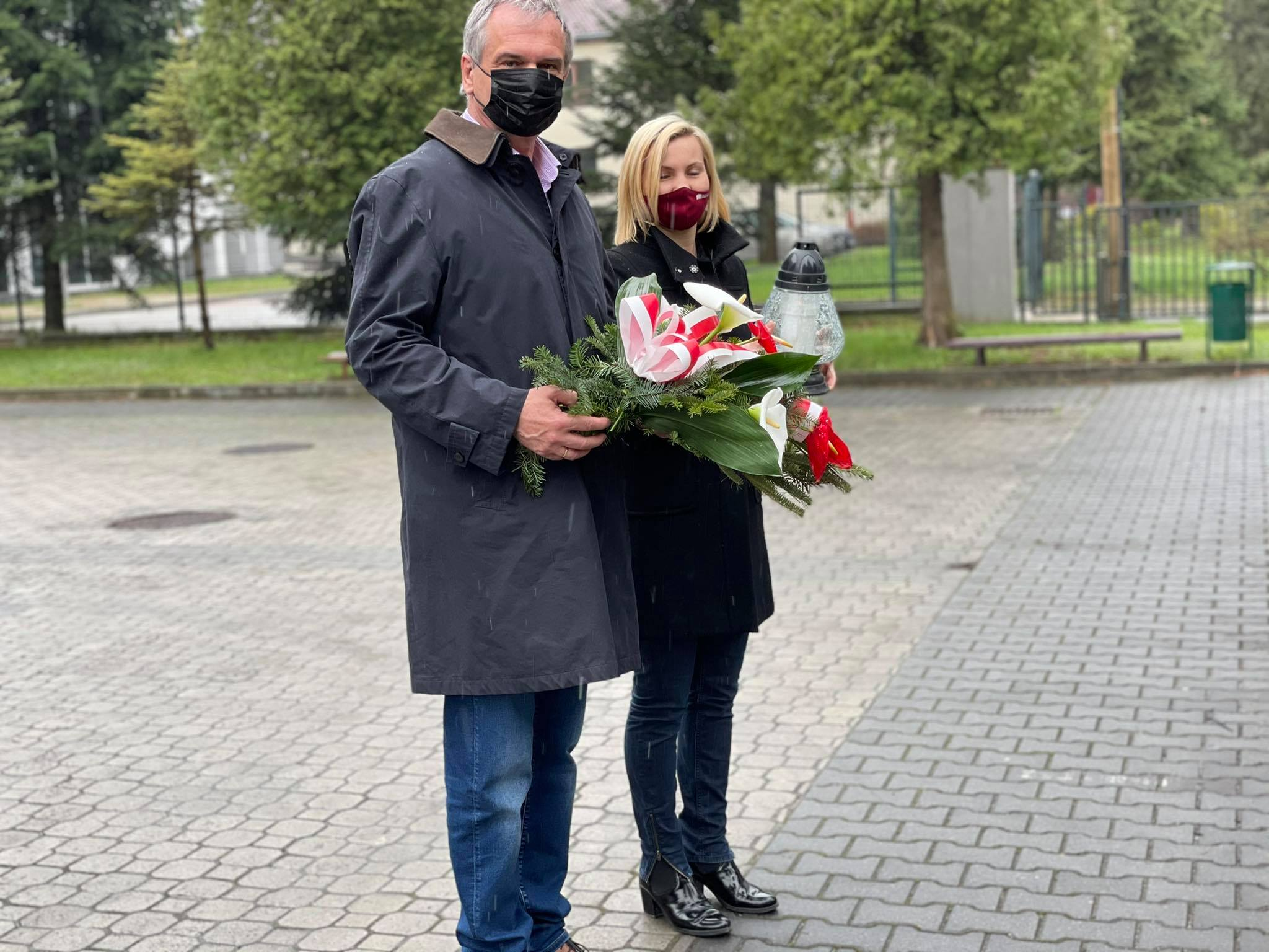 kobieta i mężczyzna z kwiatami i zniczem przed pomnikiem ofiar Katynia