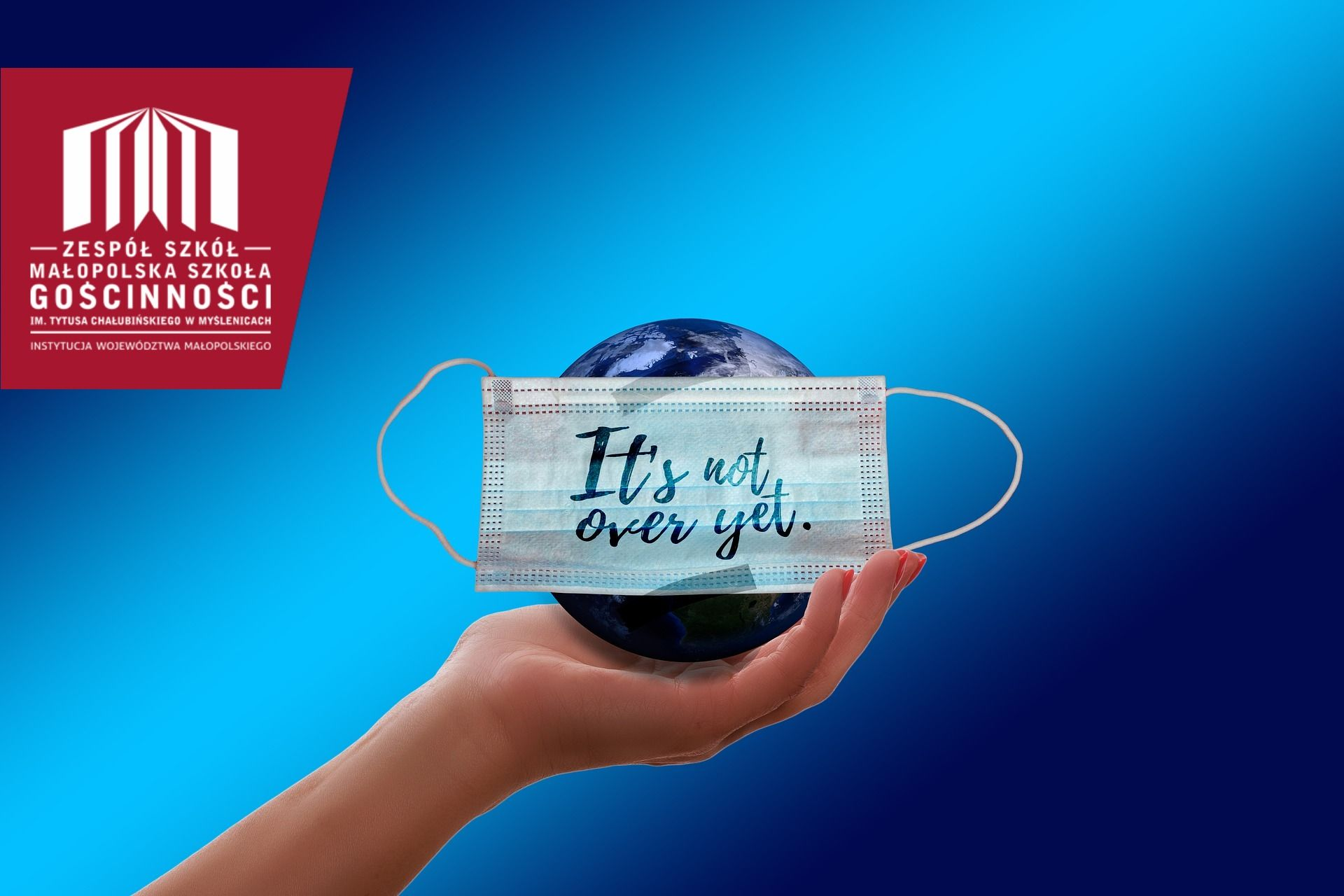 """Dłoń trzymające glob w maseczce z napise w języku angielskim""""to nie koniec"""""""