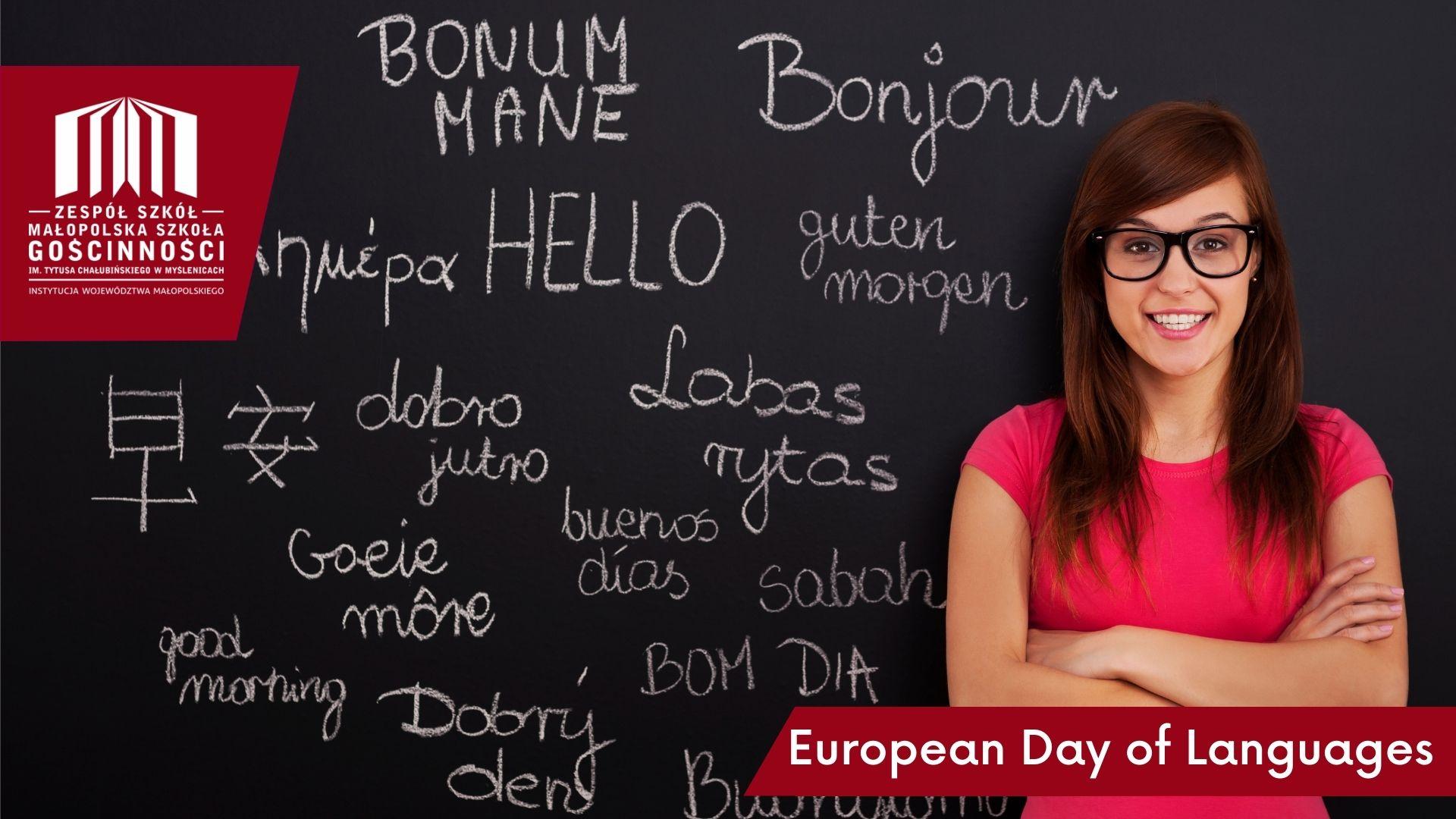 Kobieta z długimi ciemnymi włosami, w okularach i różowej koszulce, stoi z założonymi rękami. W tle czarna tablica z białymi napisami w różnych językach.